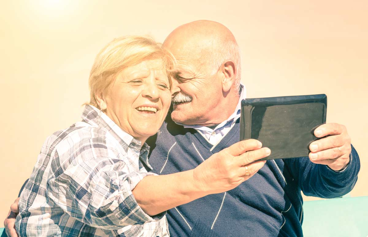 Older couple on tablet saving for retirement